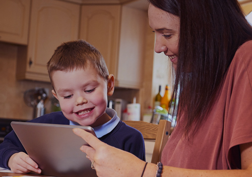 Young boy using device to learn from home